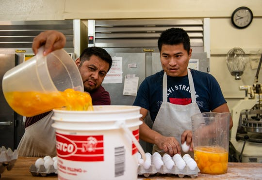Ismael Javier, left, pours over a jug filled with eggs to prepare for the multiple orders coming in for Dia de Los Muertos. The eggs will be used to make pan de yema which is a traditional bread used in Oaxaca, for Dia de Los Muertos at La Soledad Bakery in Salinas, Calif, on Wednesday, Oct. 30, 2019.