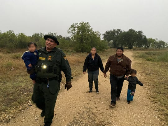 Border Patrol agents at the Uvalde Station escort a Honduran family of four out of cold, rainy weather conditions Oct. 26, 2019.