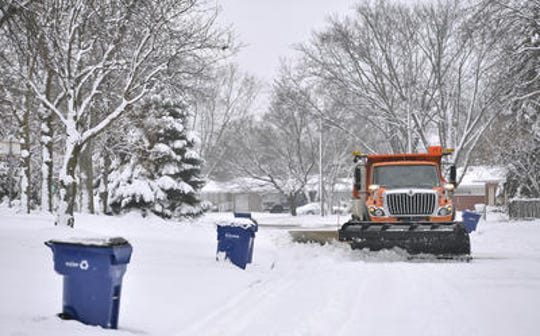 A St. Cloud snowplow driver makes his way down residential streets, dodging garbage bins in the Centennial neighborhood in December 2016.