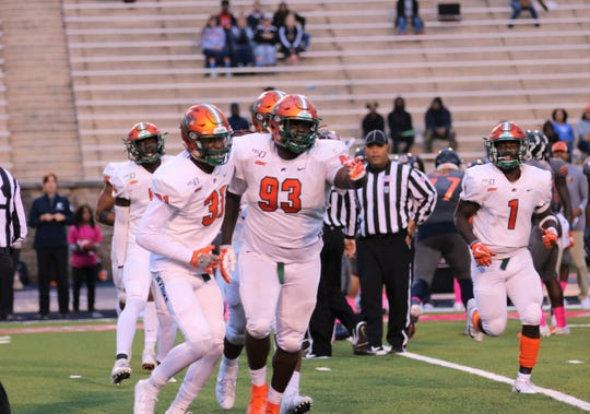 FAMU defensive lineman De'Montre Moore (93) celebrates a big play against Morgan State with Isiah Land (left) and Terry Jefferson (1).