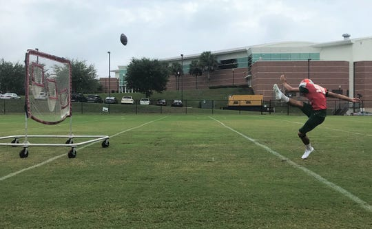Yahia Aly practices getting height on his field goal attempts by kicking over a quarterback throwing net.