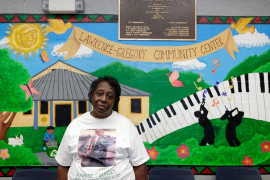 Helen Gainous, mother of Sylvester Davis Jr. who was shot and killed in his home 14 years ago, poses for a photo in front of a mural in the Lawrence-Gregory Community Center where her son's portrait is painted in the sun.