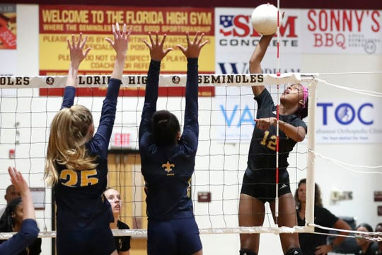 Florida High Seminoles outside hitter Keionna Mackey (12)swings outside the block. Florida High swept Trinity Prep to move onto the Region 1-3A Finals.