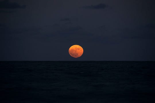The full moon rises over the Atlantic Ocean on Sunday, Oct. 13, 2019, at Ross Witham Beach near the House of Refuge Museum at Gilbert's Bar in Martin County. The location is a popular spot for sky watching during the full moon, as the sun sets in the west over the Indian River Lagoon, quickly followed by the rising moon in the east over the ocean.