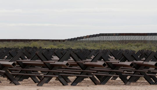 Vehicle barriers in the foreground which were removed to make way for the second generation of 18-foot bollard fencing, background left, and the new 30-foot fence which is currently under construction in New Mexico.