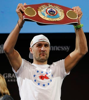 Sergey Kovalev holds up his belt during a news conference Wednesday in Las Vegas. Kovalev is scheduled to fight Canelo Alvarez in a WBO light heavyweight title bout Saturday.