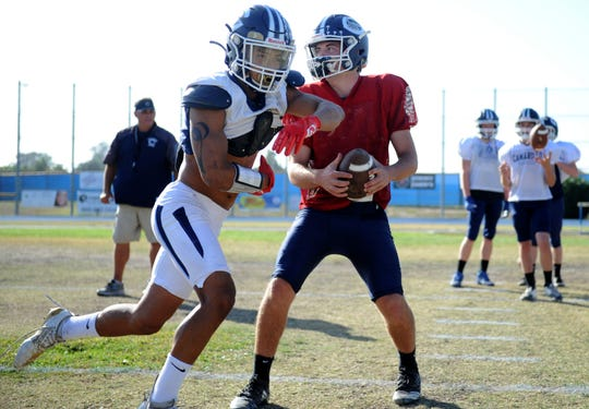 Quarterback James McNamara fakes a handoff to running back Jesse Valenzuela during Camarillo's practice Tuesday. The duo have led the Scorpions to a 9-0 record before Friday night's Camino League clash with Grace Brethren.
