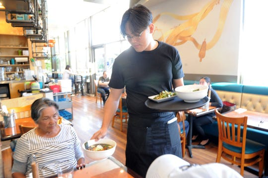 Doris Caplan, of Thousand Oaks, is served her lunch from waiter Prach Prasertwit at Tsuki Ramen in Westlake Village.