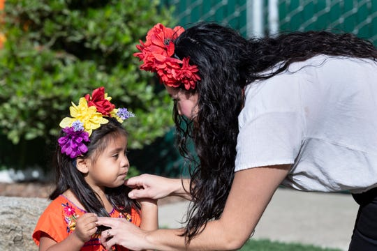 Jessica Rivera helps her daughter Ada Marie Rivera with flowers in her hair Wednesday, October 30, 2019. A Dia De Los Muertos (Day of the Dead) celebration is planned at the Visalia Public Cemetery on Saturday, Nov. 2. The Tulare County League of Mexican American Women host the free event. It starts at noon with a blessing performed by Aztec dancers, followed by a variety of folkloric dancers throughout the day. Altars, craft booths and food vendors will be on site.