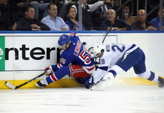 Luke Witkowski #28 of the Tampa Bay Lightning checks Ryan Lindgren #55 of the New York Rangers into the boards during the first period at Madison Square Garden on October 29, 2019 in New York City.
