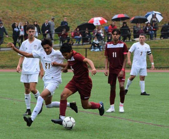 Ossining's Jaime Soria holds off Arlington's Michael Cocca and advances the ball while J.P. Estupinan (11) looks on in the first half of a 2-1 win in a Section 1 Class AA semifinal on Oct. 30, 2019 at Ossining High School.