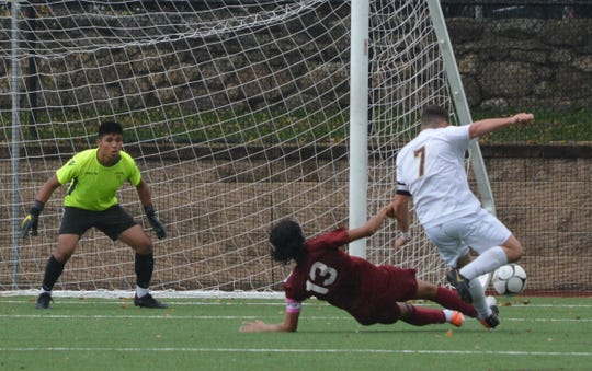 A sliding tackle by Ronald Suscal (13) takes the ball off the foot of Arlington's Franco Colantuono during the first half of Ossining's 2-1 Section 1 Class AA semifinal win on Oct. 30, 2019 at Ossining High School.