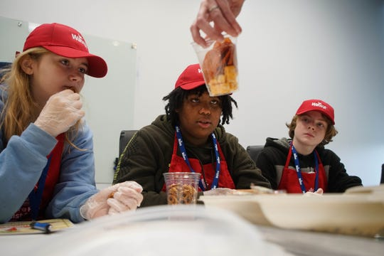 (left to right)Arissa Wilson, Jasmine Wilson and Joey Golembiewski, all eighth graders at P.S. DuPont Middle School, try to guess the nutritional values from food they selected to put together in a snack during in a half day innovation summit where they learned about the science that is a part of food creation at Wawa's headquarter's in Media, Pa, on Wednesday, Oct. 30, 2019.