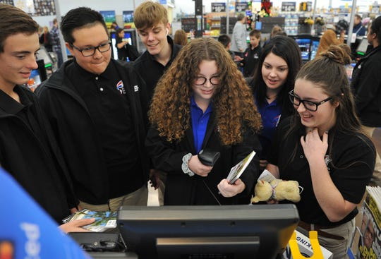A group of students from Wichita Christian School gathered at the Walmart self-check-out to take turns ring-up gifts they had gathered to box and ship to disadvantaged children living in Zambia, Wednesday afternoon.