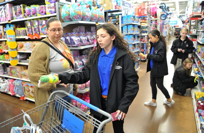 Seventh grade Wichita Christian School student Kaitlyn Foster, centered, with fellow students and teachers shopped for Christmas gifts to be, that will be boxed and shipped to impoverished children living in Zambia.