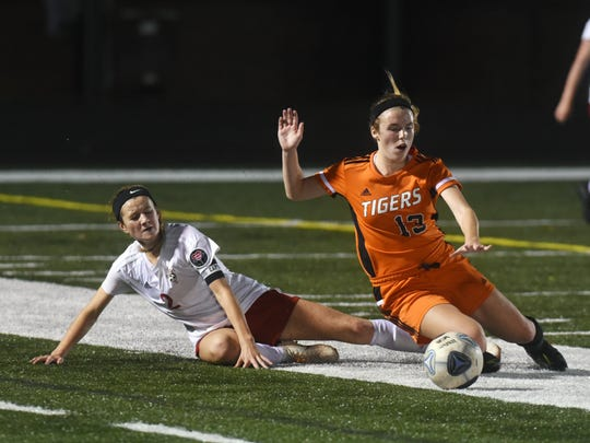 Rosecrans' Kailee Zemba, left, makes a slide tackle against Grace Venturella during a 1-0 win against New Middletown Springfield on Tuesday night at Canton Central Catholic.