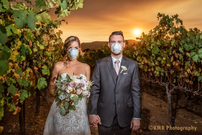 Curtis and Katie Ferland — who traveled from Chicago to have their dream destination wedding in Sonoma County, California — were photographed hand-in-hand with masks over their mouths to protect them from smoke as the Kincade Fire raged in the background.