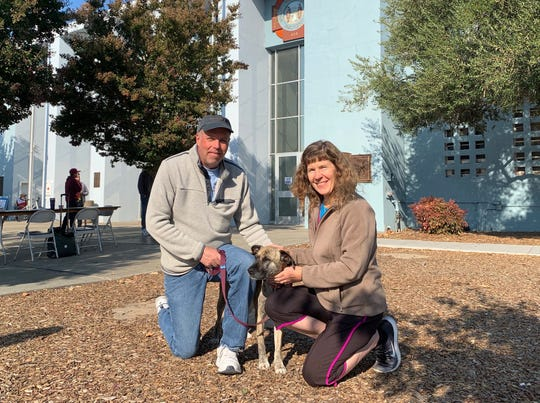 Gail (left) and Allison Baker, with their dog Muffin. The family, which includes the couple's teen daughter, were evacuated from their home near Santa Rosa due to the Kincade Fire, and are finding food and shelter at a Red Cross administered shelter in town.