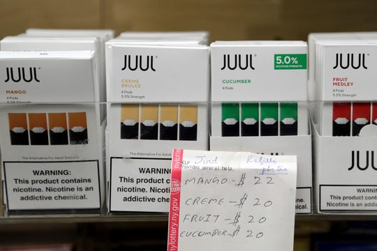 In this Thursday, Dec. 20, 2018 file photo, Juul products are displayed at a smoke shop in New York. On Thursday, Oct. 17, 2019, the company announced it will voluntarily stop selling its fruit and dessert-flavored vaping pods.