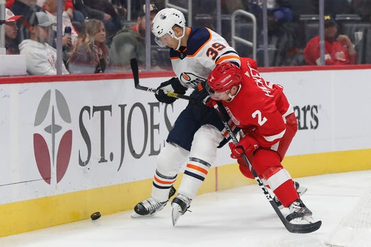 Edmonton Oilers right wing Alex Chiasson, left, and Detroit Red Wings defenseman Joe Hicketts battle for the puck in the first period at Little Caesars Arena in Detroit.