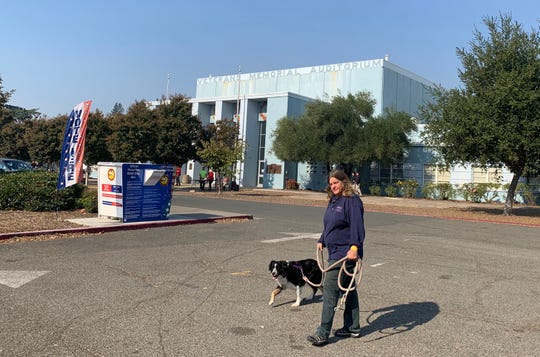 Cindy Baldwin walks her dog Lucy across from the Santa Rosa Veterans Memorial Auditorium, where the Red Cross is administering a shelter for evacuees from the Kincade Fire.