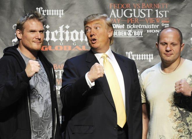 Then-real estate mogul Donald Trump  poses with Mixed Martial Art (MMA) heavyweight fighters US Josh Barnett (L) and Russia's Fedor Emelianenko in 2009.