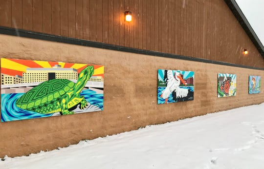 """Four murals titled """"Wonderful Wisconsin Wildlife"""" hang on the north side of the Washington Park Shelter in Neenah. They were created by artist Ben Erickson."""
