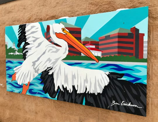 A mural created by Neenah native Ben Erickson depicts a pelican flying over water near several Neenah landmarks. The painting and three others are mounted on the north side of the Washington Park Shelter in Neenah.