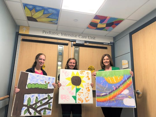 Hannah Donner (center) presents painted ceiling tiles to Jersey Shore University Medical Center's K. Hovnanian Children's Hospital, which saved her life after a car accident.