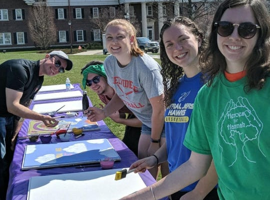 Students at The College of New Jersey at a painting party for Hannah Donner's ceiling tiles.