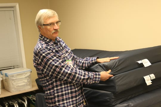 Roland Arper, an emergency winter shelter manager, shows bedding at the Port Orchard United Methodist Church on Wednesday.