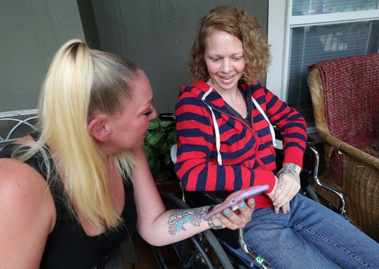 Jacinta Nall, left, shows photos to her sister Tessa. Tessa has four children, ranging in age from 10 to 18.
