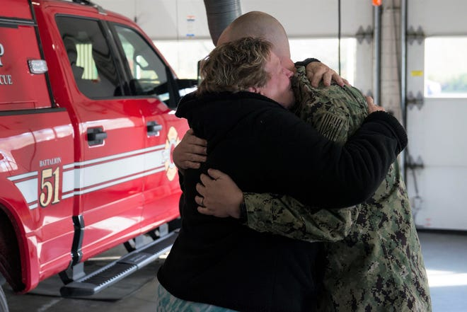Dawn Ruth cries and hugs Dylan Lapinski, a Master Chief Petty Officer on the USS Pennsylvania submarine, who saved her from her home as it burned while he was passing by on his way to work Wednesday.