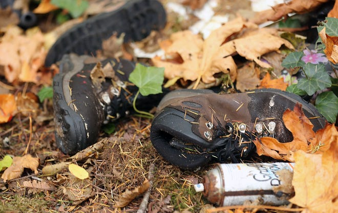 Shoes are seen among the leaves and trash at an abandoned homeless encampment along Black Jack Creek in Port Orchard in October.