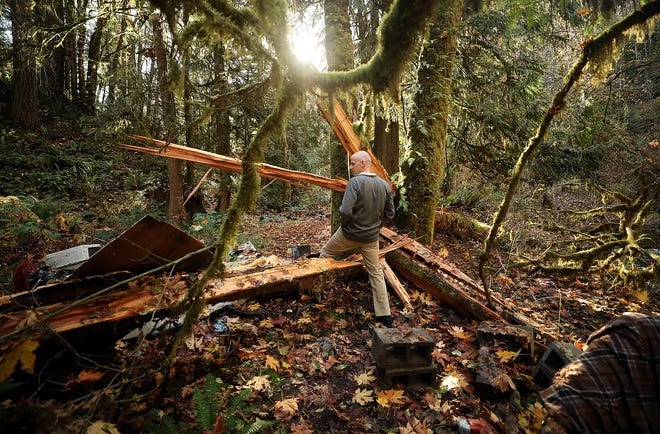 Patrick Hamel, environmental health specialist with Kitsap Public Health District, steps over a fallen tree as he looks over an abandoned homeless encampment along Blackjack Creek in Port Orchard on Wednesday.