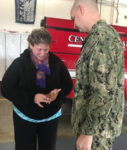 "Dawn Ruth cries as Master Chief Petty Officer Dylan Lapinski gives her a Navy ""challenge coin"" after saving her from a house fire on Wednesday."