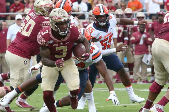 Florida State's Cam Akers, left, runs against Syracuse defense during an NCAA college football game, Saturday, Oct. 26, 2019 in Tallahassee, where FSU won 35-17.