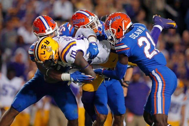 Florida linebacker David Reese II, left, defensive back Donovan Stiner and defensive back Trey Dean III (21) upend LSU tight end Stephen Sullivan (10) on a reception in the first half of game on Oct. 12. The Gators' defense will get a lift when two pass rushers return from injuries this week.