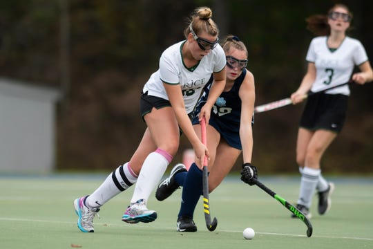 Rice's Kate Buckley (16) plays the ball past MMU's Madi Cohen (12) during the field hockey semifinal game between the Mount Mansfield Cougars and the Rice Green Knights at Middlebury College on Wednesday afternoon October 30, 2019 in Middlebury, Vermont.