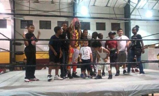 Hot Dog, aka Michael Starkes, takes a photo in the ring with children who came to see a pro wrestling show recently in Camden.