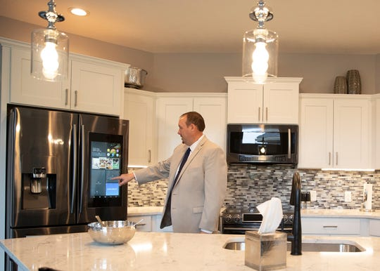 Courtyards at Deer Run developer Kevin Norman demonstrates a smart panel TV in a refrigerator that is one of the options available to residents who chose to live in the new customizable community.