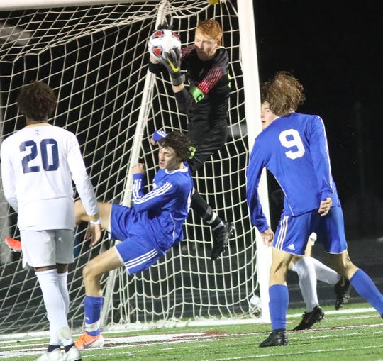 Moeller goalie Cal Collins (0) goes up for a save during their regional semifinal against St. Xavier Wednesday, Oct. 30, 2019.