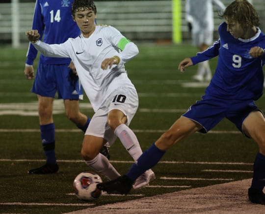 Moeller player Parker Grinstead (10) battles St. Xavier player John Schaeper for the ball during their regional semi-final Wednesday, Oct. 30, 2019.