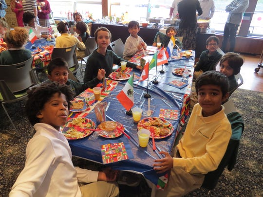 Second grade students and their parents enjoy delicacies from around the world in the school's Oakwood Room, which was transformed into a United Nations setting.
