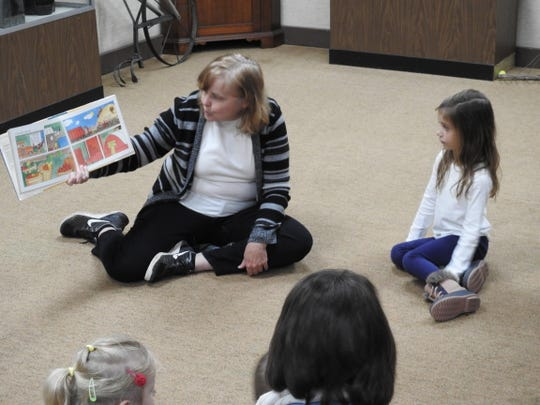"Karen Chanay reads ""Farming"" by Gail Gibbons to 14 children, including 4-year-old Allie Miller, and their guardians during the Down on the Farm program for preschoolers Thursday at the Johnson-Humrickhouse Museum."
