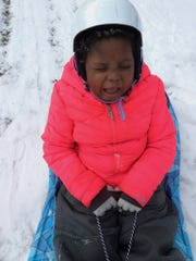Chika makes a funny face while sledding.