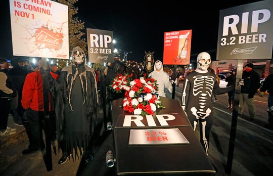 A ghoulish group of pallbearers stand in front of a casket representing 3.2% beer, Wednesday, Oct. 30, 2019, in Salt Lake City. After 86 years, this Halloween marks the last day 3.2% beer will be sold in Utah stores. Beginning Nov. 1, Utah stores will be selling up to 5% ABV beer, and Budweiser wants to celebrate with a funeral complete with their famous Clydesdales, in the background.