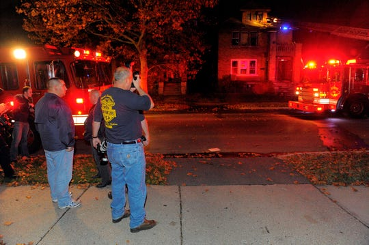 Photographers take photos of a fire near the corner of Waveney and Dickerson during Angels' Night, Friday Oct. 30, 2009, in Detroit's east side.