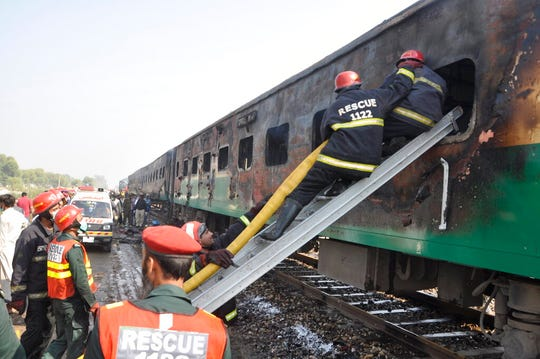 Rescue workers look for survivors following a train damaged by a fire in Liaquatpur, Pakistan.
