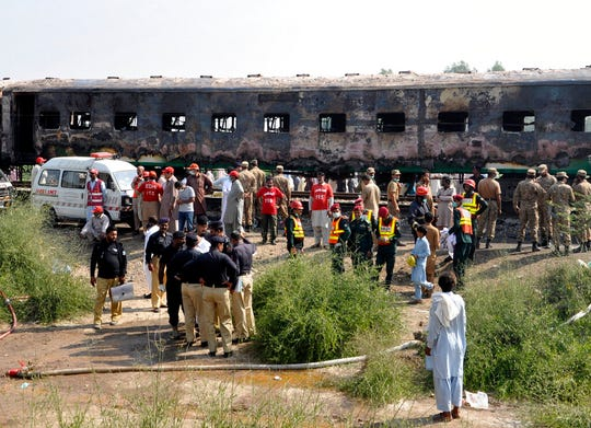 Pakistani soldiers and officials examine a train damaged by a fire in Liaquatpur, Pakistan, Thursday, Oct. 31, 2019.